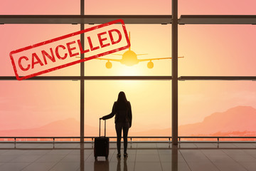 Young woman with suitcase in the departure hall at airport. Flight cancelled. Coronavirus-COVID-19. Epidemic virus 2019-nCoV Respiratory Syndrome. Medicine concept.
