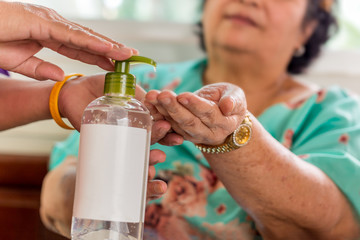 Senior woman applying alcohol gel in hand to preventing germs, coronavirus.