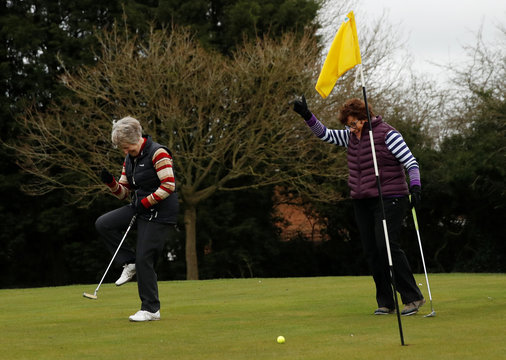 Sheila Carter and Linda Buckingham react on a green at Windmill Hill Golf Centre