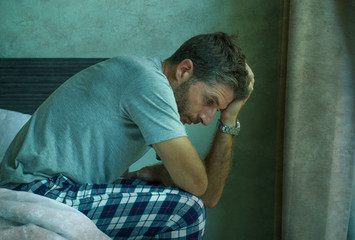 dramatic portrait of attractive scared and depressed 40s man on bed in pajamas feeling worried suffering anxiety and depression during virus quarantine home lockdown