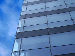 the corner of a modern glass office building next to a blue sky with white clouds