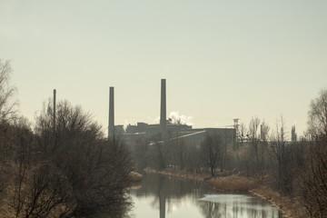 Fototapeta Wolno płynąca rzeka na tle kominów fabryki. obraz