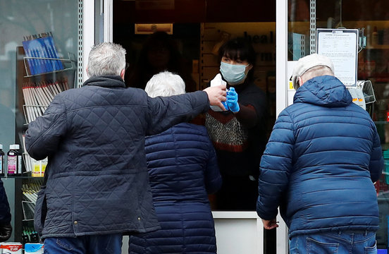 Customers collect their prescriptions outside a pharmacy in Belfast