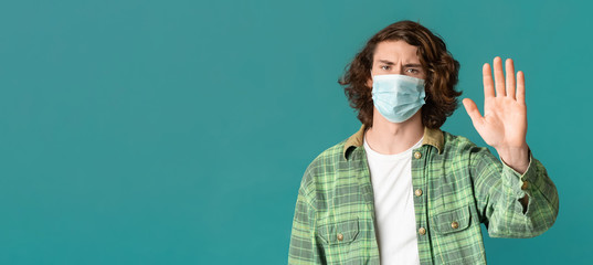Millennial guy in mask making STOP gesture, protesting against epidemic on color background, copy space. Panorama