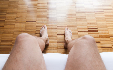 Bare feet of a man sitting in a bed