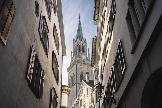 Low angle shot, between two buildings, of a steeple of St. Gallen Cathedral in Switzerland