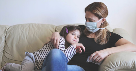 sick mother with surgical mask stay with her child on the sofa