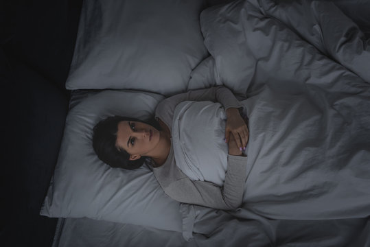 top view of woman with sleep disorder lying in bedroom