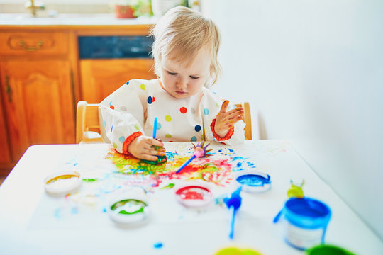Adorable little girl painting with fingers
