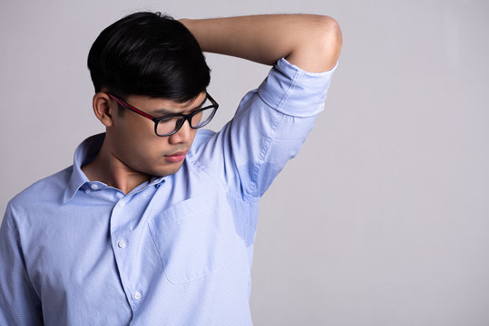 Close up asian man with hyperhidrosis sweating. Young asia man with sweat stain on his clothes against grey background. Healthcare concept.