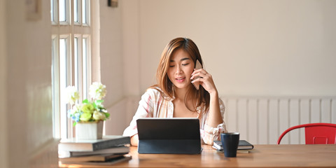 Photo a beautiful woman using a smartphone to calling someone while sitting in front a computer tablet with keyboard case at wooden working table over comfortable living room as background.