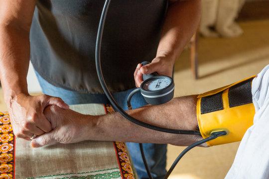 Prise de tension artérielle par aide-soignante soins infirmiers à domicile