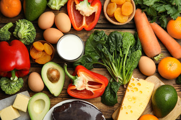 Fresh products rich in vitamin A on wooden table, flat lay
