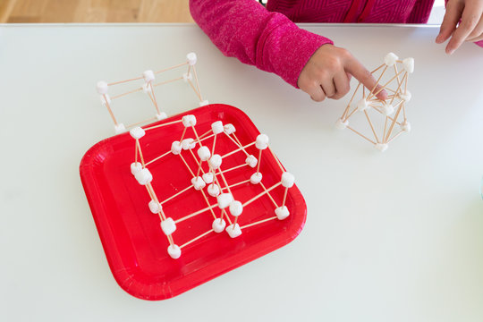 Closeup of child building three dimensional structures out of marshmallows and toothpicks for STEM lesson