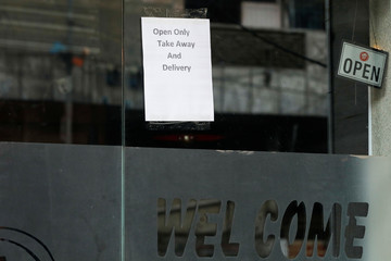 A note is seen outside Pizza Hut food outlet, after Sindh provincial government decided to shut markets, restaurants, public beaches and discouraged large gatherings amid the outbreak of the coronavirus disease (COVID-19), in Karachi