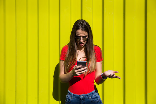 Young woman using mobile phone by the yellow wall