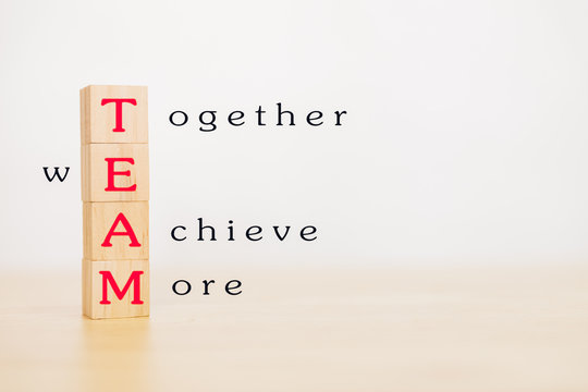 Motivation and Teamwork concept. Wooden block stack up and word TEAM on wooden table. With copy space for your text.