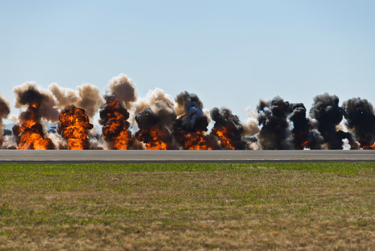 Multiple firey explosions with thick black smoke on an airport runway.