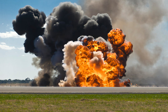 Firey explosion with thick black smoke on an airport runway.