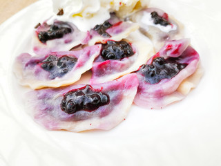 Fototapete - delicious sweet polish dumplings stuffed with blueberries jam and blueberries for toppings served with vanilla ice cream and Whipped cream in white plate