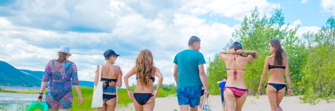 Russia Samara July 2019: A large family walks along the sandy beach on a summer day.
