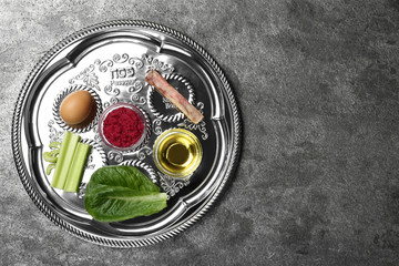 Passover Seder plate (keara) on grey table, top view with space for text. Pesah celebration
