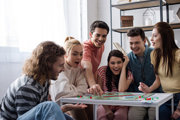 KYIV, UKRAINE - JANUARY 27, 2020: excited young friends playing monopoly game at home