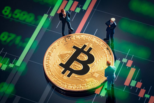 Business meeting about the investment decision for bitcoin concept: Macro miniature businessman figurines standing near the shiny golden bitcoin. Colorful stock market graphic chart on background.