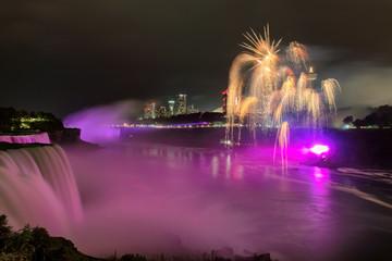 Niagara Falls lit at night by colorful fireworks, Niagara Falls, NY, USA.
