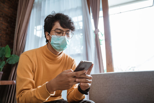 portrait of sick man wearing medical masks using mobile phone during virus epidemic lockdown. social distancing concept on corona virus