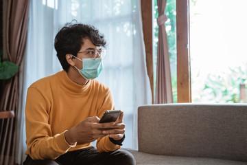 portrait of sick man wearing medical masks using mobile phone during virus epidemic lockdown....