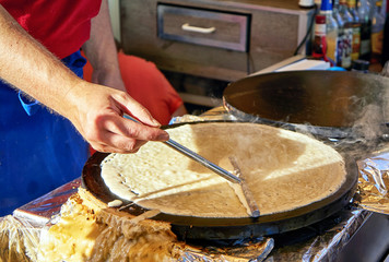 Making crepes pancakes at a market. A hand makes crepes on a metal grill with a stick.