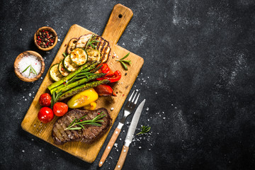 Beef steak grilled with vegetables on black stone table.