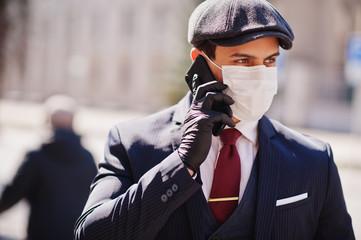 Concept of coronavirus quarantine. Business man wear on suit and cap with medical face mask, speak on phone. MERS-Cov, Novel coronavirus 2019-nCoV