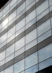 vertical perspective view of the facade of a modern glass commercial building with steel frames and sky reflected in the windows