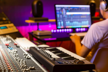 back of male asian professional producer working in recording studio, focus on mixing console fader. music production concept