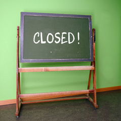 Closed written on an old school chalkboard to symbolize the closure of schools as preventive measure during the risk of infection with the curonavirus