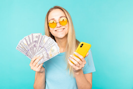 young lady isolated over blue background. Looking camera showing display of mobile phone holding money.