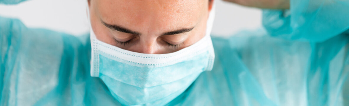 Woman doctor wearing protection face mask against coronavirus. Banner panorama medical staff preventive gear.