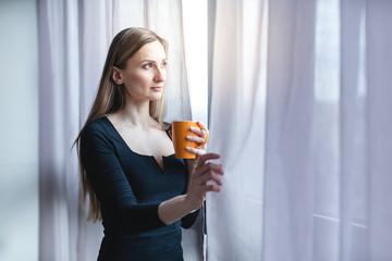 Frau steht mit Kaffee allein am Fenster während der Covid-19 Ausgangssperre