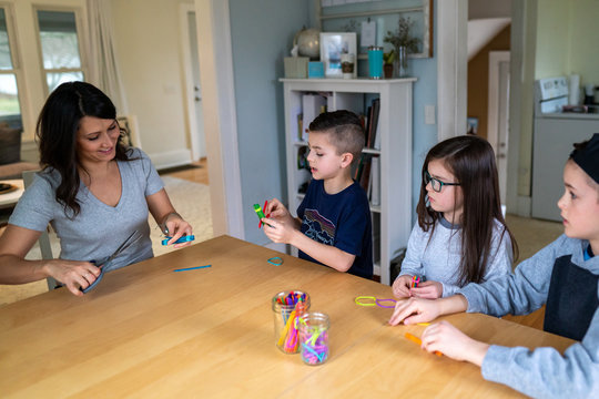 Mother showing children how to build a catapult out of popsicle sticks and rubberbands as part of a homeschool STEM lesson