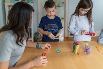 Children building catapults with popsicle sticks and rubberbands as part of a homeschool STEM lesson