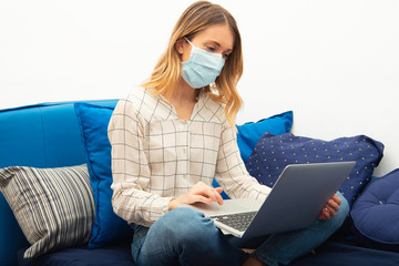 Young business woman working from home with laptop, wearing protective mask