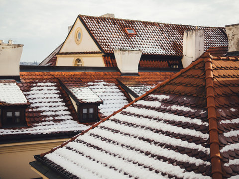 Red old tile roofs of houses with snow