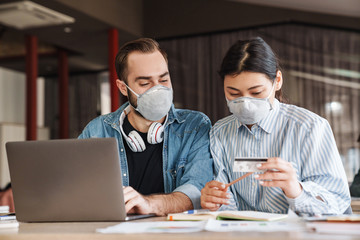Photo of students in medical masks holding credit card while studying