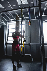 Woman doing fitness workout in gym, exercise on TRX straps