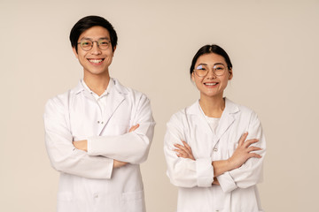 Image of asian young medical doctors in white uniform smiling together