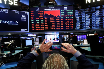 A trader takes a picture of screens displaying trading information over the floor of theNewYorkStockExchange(NYSE) inNewYork