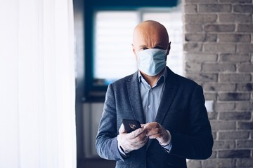 Businessman wearing protective medical mask and using smartphone at home.