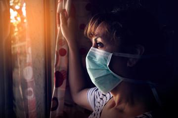 Mujer mirando desde el interior de su casa. No puede salir por el coronavirus Wall mural